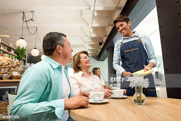 waitress serving couple at a restaurant - serving size stock photos and pictures