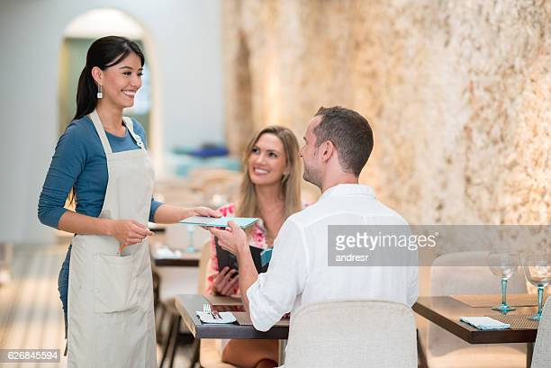 Waitress serving couple at a restaurant
