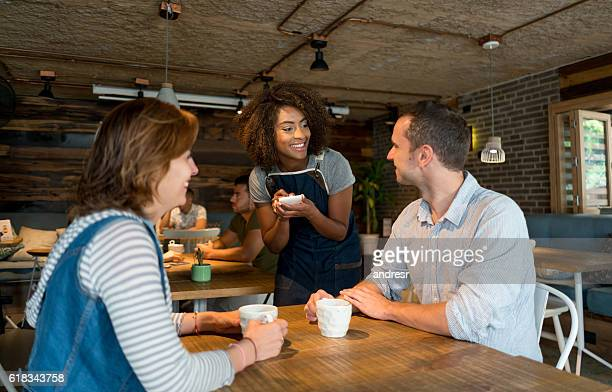 waitress serving customers at a restaurant - waitress stock pictures, royalty-free photos & images