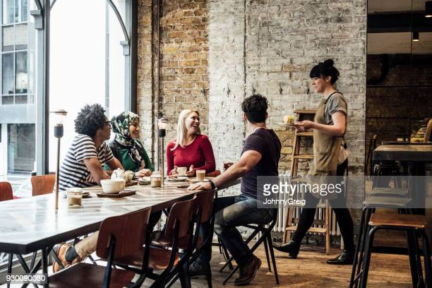 waitress serving customers in cafe - restaurant stock photos and pictures