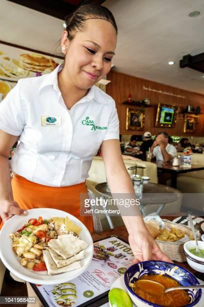 A waitress serving food at La Casa de los Abuelos restaurant