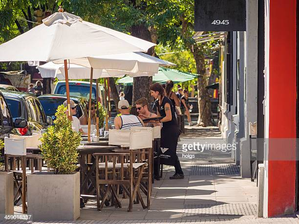 waitress serving food at outdoor restaurant, buenos aires, argentina - palermo buenos aires stock photos and pictures