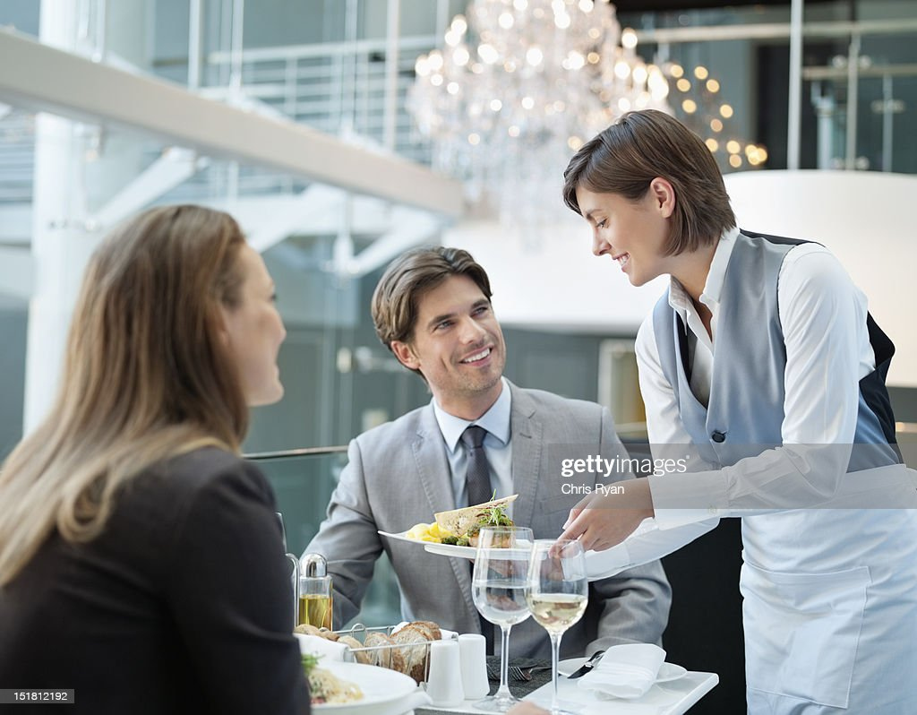 Waitress serving food to couple in restaurant : Stock Photo