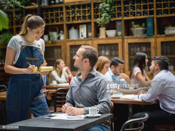 waitress serving man at a restaurant - wait staff stock pictures, royalty-free photos & images