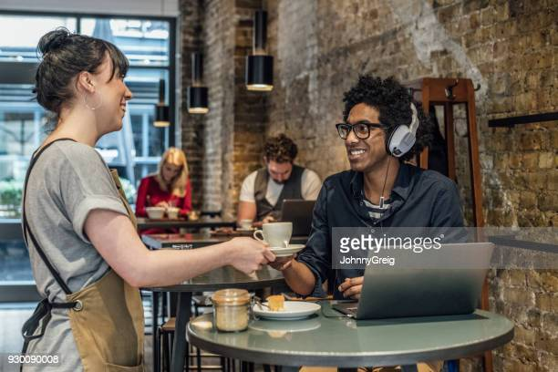 Waitress serving man coffee in cafe and smiling