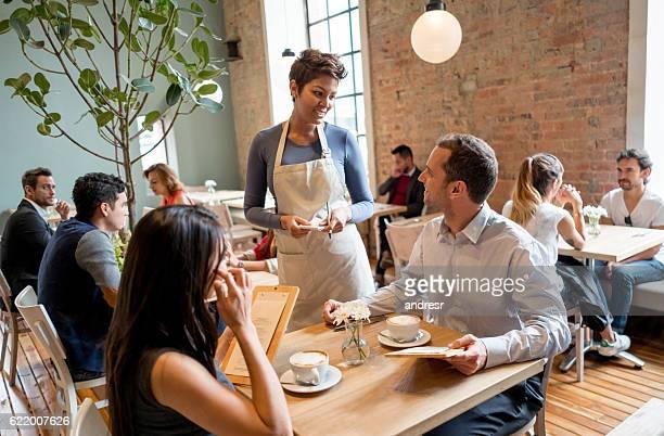 waitress serving people at a restaurant - porção de comida - fotografias e filmes do acervo