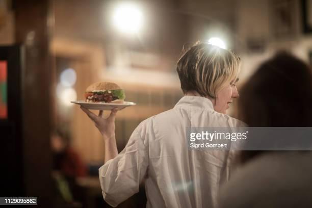 waitress serving plate of burger in gastro pub - sigrid gombert stock-fotos und bilder
