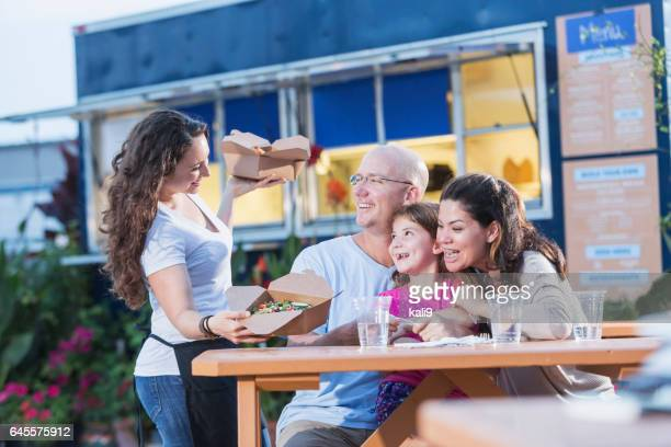 waitress serving to customers outside food truck - serving food and drinks stock pictures, royalty-free photos & images