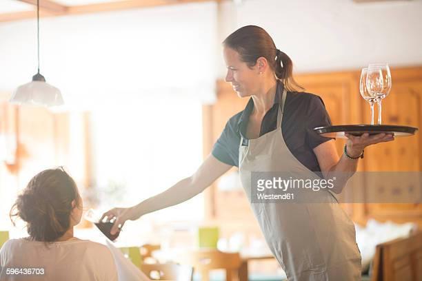 Waitress serving wine in restaurant