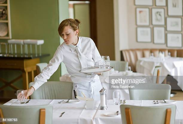 waitress sets out water glasses in restaurant - wait staff stock pictures, royalty-free photos & images