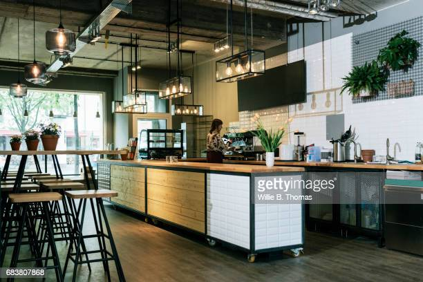waitress sets up and prepares for customers at a business cafe - comptoir de bar photos et images de collection