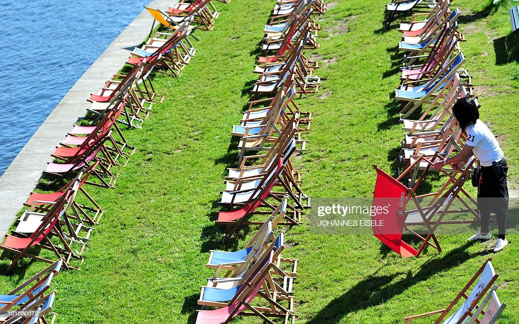 A waitress sets up deck chairs at a bar on the banks of the river Spree on June 3, 2010 in Berlin. Summer finanlly starts in Germany on June 3, 2010, after weeks of cold and rainy weather.