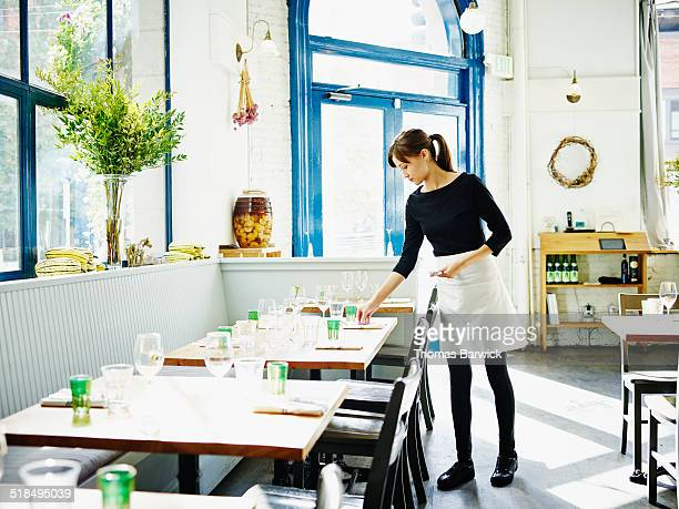 waitress setting table in restaurant - wait staff stock pictures, royalty-free photos & images