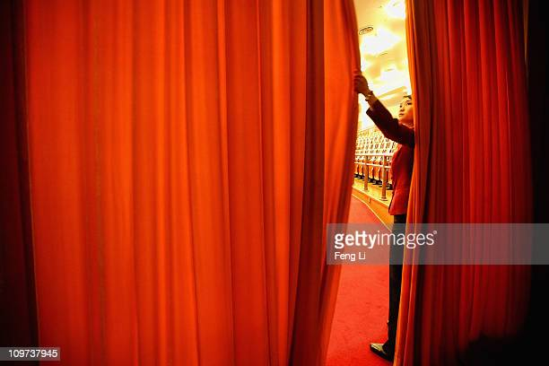 A waitress shelters from the entry with the curtain during the opening ceremony of the Chinese People's Political Consultative Conference at the...