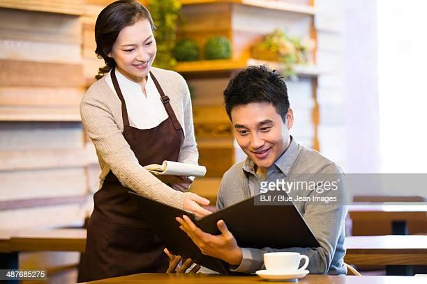 Waitress showing menu to customer