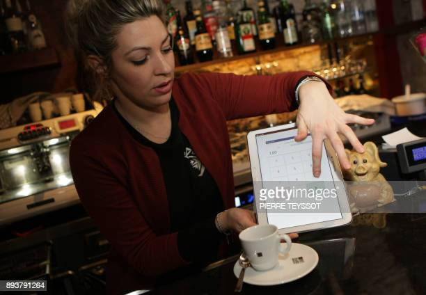 A waitress shows how to pay a coffee with bitcoins on December 11 2017 at the bar 'Mani al Cielo' in Rovereto northern Italy Bitcoin surged past...