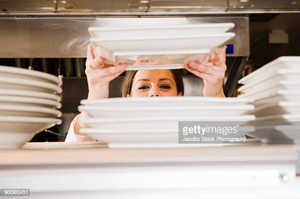 Waitress Stacking Plates in Restaurant