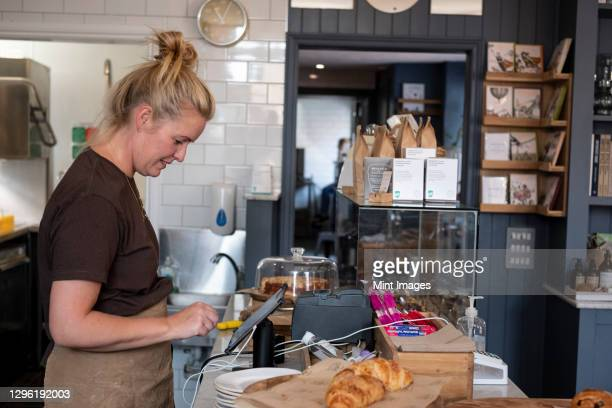 waitress standing at counter in a cafe, working the till. - mature women stock pictures, royalty-free photos & images