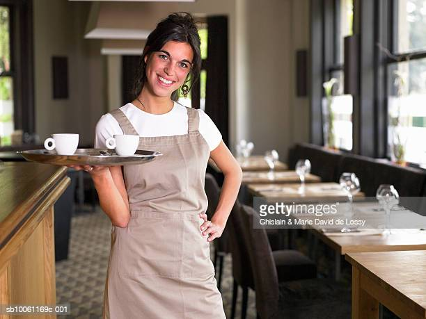 Waitress standing with two cups of coffee on tray in cafe, portrait