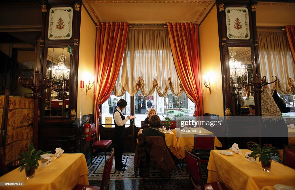 A waitress takes customers' orders at a table inside Caffe Baratti in Turin, Italy, on Tuesday, Jan. 29, 2013. Italy sold 8.5 billion euros ($11.4 billion) of six-month Treasury bills as rates dropped to the lowest in almost three years as the European Central Bank's pledge to buy bonds continues to provide an effective backstop even amid rising political concerns. Photographer: Alessia Pierdomenico/Bloomberg via Getty Images