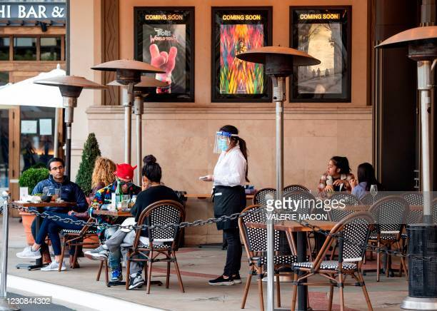 Waitress takes customers' orders in the outdoor seating area of a restaurant on January 28, 2021 in Los Angeles. - California lifted blanket...