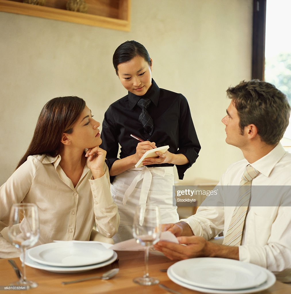 waitress taking an order from a young couple in a restaurant : Stock Photo