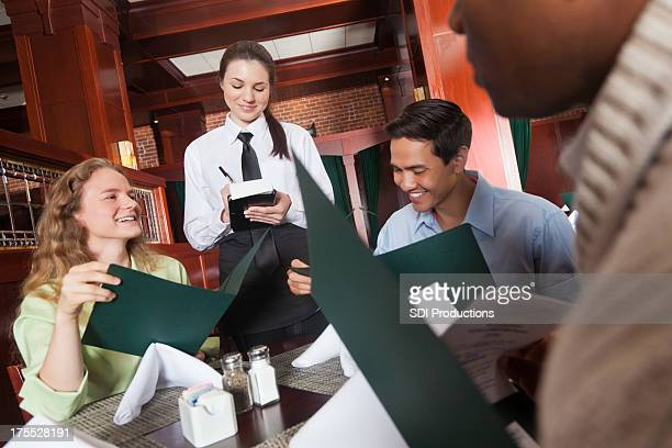 Waitress taking food orders from diverse group of diners