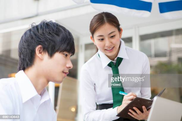 Waitress taking order from young man
