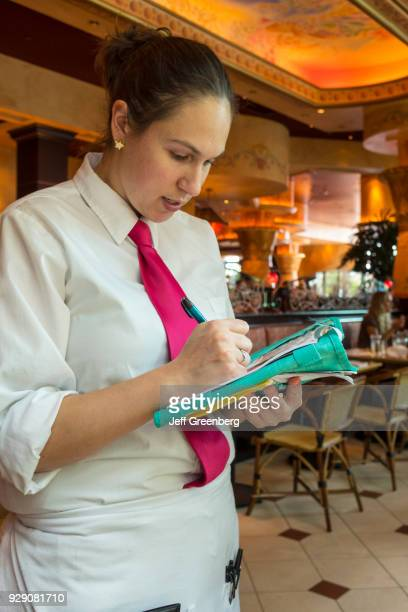 A waitress taking order in the Cheesecake Factory at The Mall at Millenia