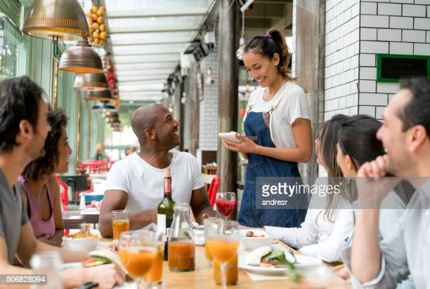 Waitress taking orders to people at a restaurant