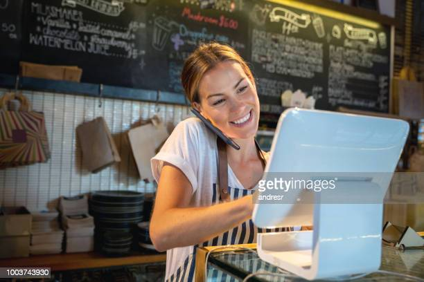 waitress talking on the phone at a restaurant - business owner stock pictures, royalty-free photos & images