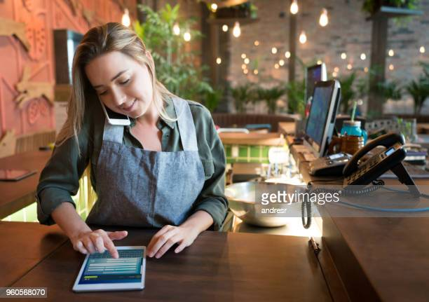 waitress talking on the phone at a restaurant - demanding stock pictures, royalty-free photos & images