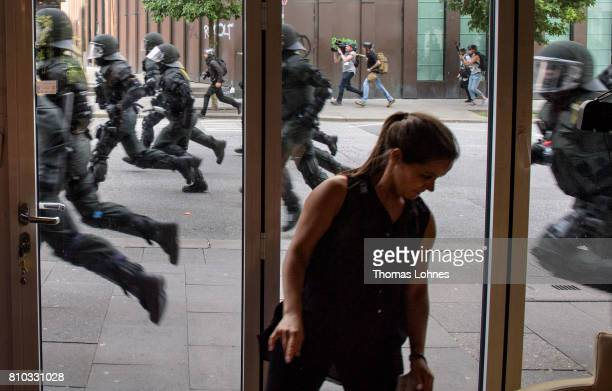 A waitress turns away from a police unit running after demonstrators during an anti G20 Summit protest on July 7 2017 in Hamburg Germany Leaders of...