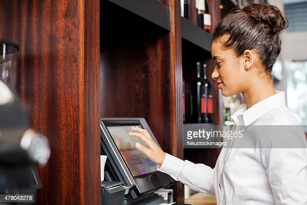 waitress using cash register in restaurant - register stock photos and pictures