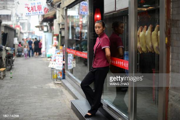 A waitress waits for customers at the entrance of a restaurant in Beijing on September 9 2013 Chinese inflation slowed to 26 percent yearonyear in...