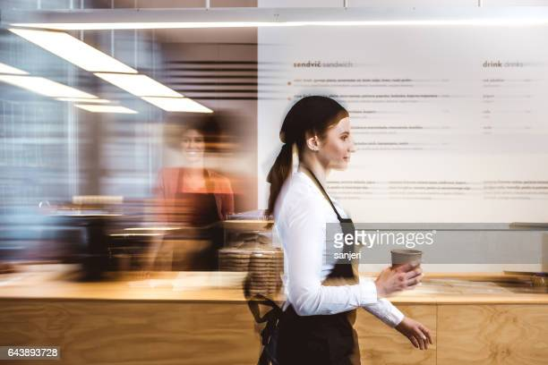 waitress walking with a cup of coffee - differential focus stock pictures, royalty-free photos & images