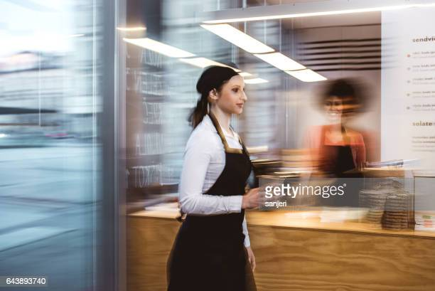 Waitress walking with a cup of coffee