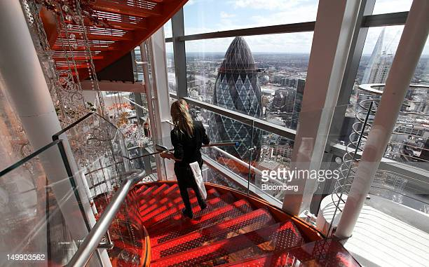 A waitress walks down a staircase past a view of the city skyline and Swiss Re tower also known as the 'Gherkin' inside the Sushisamba restaurant in...