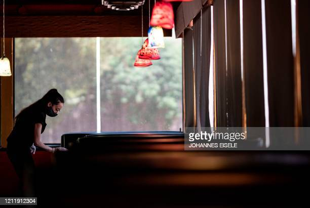 Waitress wearing a mask and gloves disinfects a table in a Restaurant on May 5, 2020 in Stillwater, Oklahoma. - In the face of intimidation against...