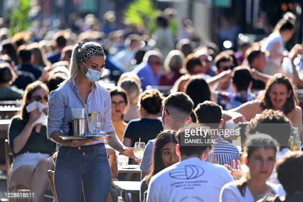 A waitress wearing a protective face covering brings drinks to customers in the late summer sunshine at outside tables in Soho central London on...