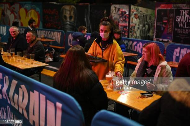 Waitress wearing a protective face covering to combat the spread of the coronavirus, brings drinks to customers sitting at a table outside a bar in...