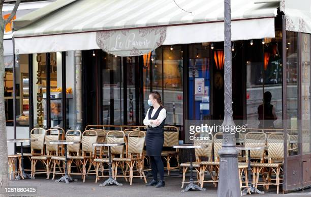 A waitress wearing a protective face mask waits for customers in front of an empty restaurant terrace near NotreDame Cathedral during the coronavirus...