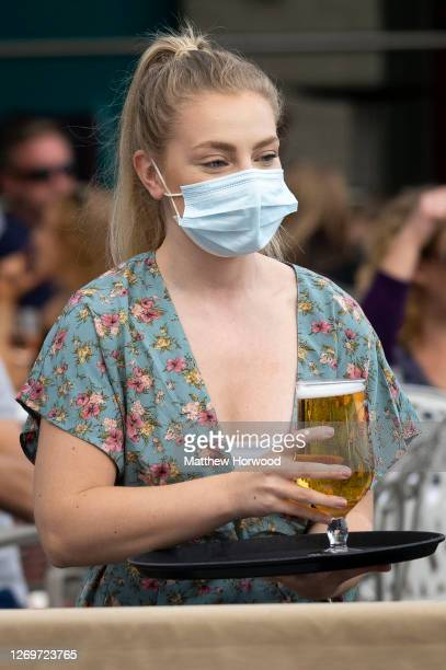 Waitress wearing a surgical face mask serves alcohol to a customer at a restaurant on August 30, 2020 in Cardiff, Wales. More thank 60m discounted...