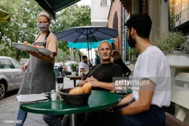 waitress wearing face mask serving food - voedingsindustrie stockfoto's en -beelden