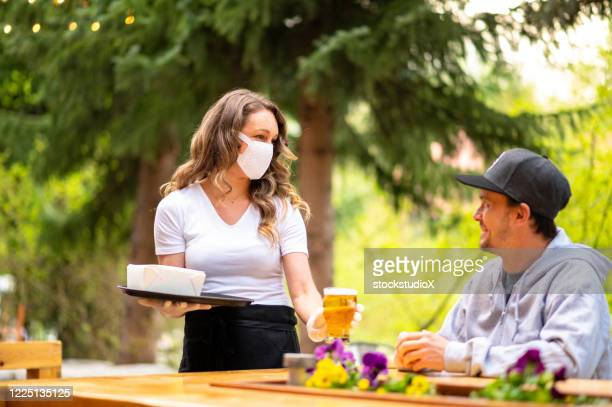 waitress wearing protective equipment for covid - social distancing stock pictures, royalty-free photos & images
