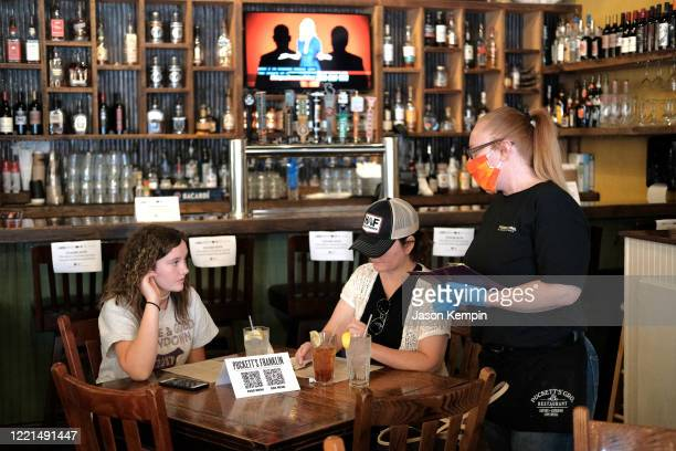 A waitress wearing rubber gloves and a mask is seen taking orders for patrons at Puckett's Grocery Restaurant on April 27 2020 in Franklin Tennessee...