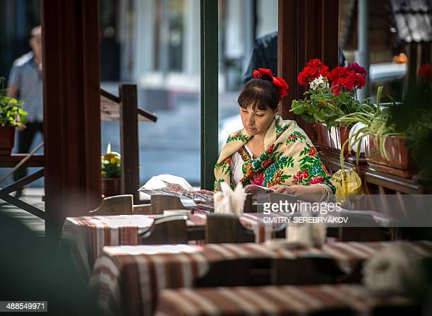 Waitress wearing Ukrainian traditional clothes reads a newspaper in the traditional restaurant in the absence of clients during a warm sunny day in...