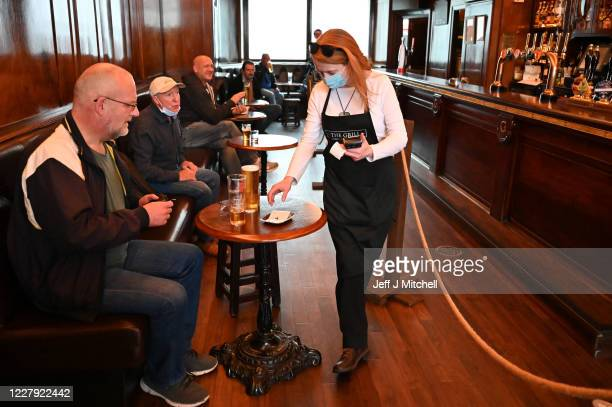 Waitress wears a mask as she works in the pub The Grill in Union Street on August 5, 2020 in Aberdeen, Scotland. Scotland's First Minister Nicola...