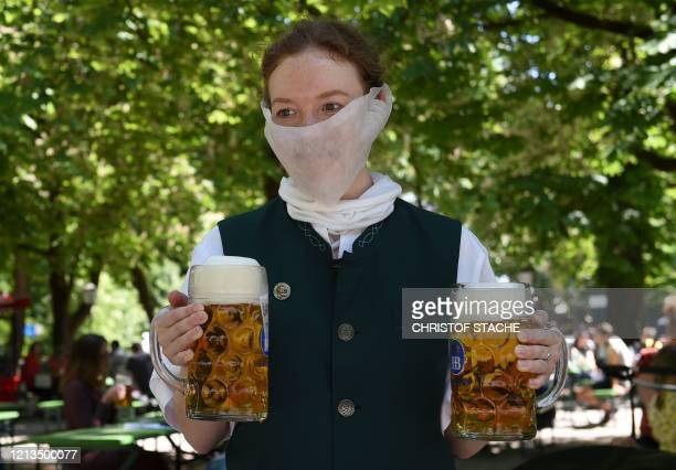 Waitress wears a protective mask and serves beer mugs in a beer garden in Munich, southern Germany, on May 18 amid the novel coronavirus Covid-19...
