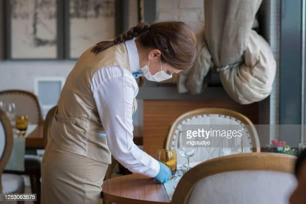 la cameriera con una maschera disinfetta il tavolo - opening event foto e immagini stock